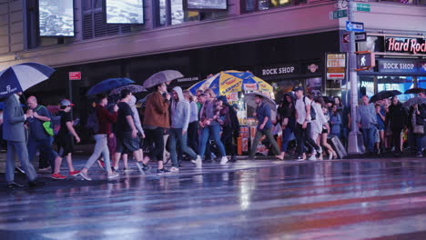 A-Crowd-Of-Pedestrians-With-Umbrellas-In-Their-Hands-In-A-Hurry-To-Cross-The-Street-In-A-Busy-Area-O