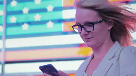 Business-Woman-Uses-A-Smartphone-On-The-Background-Of-A-Large-American-Flag-On-The-Famous-Times-Squa