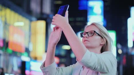 Portrait-Of-An-Attractive-Woman-Taking-Pictures-Of-Sights-In-Times-Square-It-Stands-On-The-Backgroun