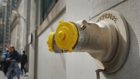 Fire-Hydrant-In-The-Wall-Of-A-Building-On-Wall-Street-In-New-York