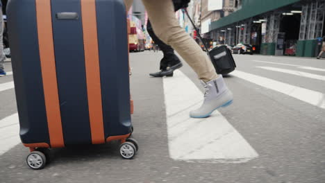 A-Person-With-A-Bag-On-Wheels-Goes-Down-The-Busy-Sidewalk-Of-Manhattan-In-New-York-Only-Legs-Are-Vis