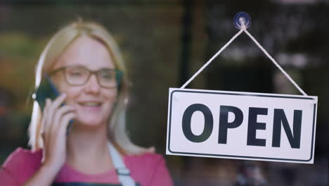 Woman-Talking-On-The-Phone-Standing-Behind-A-Glass-Door-With-A-Sign-Open
