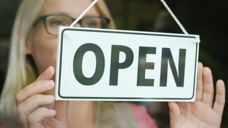 The-Female-Seller-Turns-The-Tablet-That-Says-Closed-To-Open-Beginning-Of-The-Day-Open-Your-Business-
