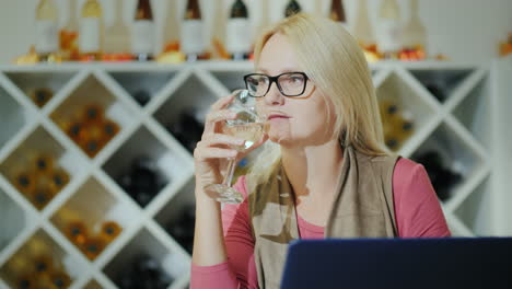 Woman-Tasting-Wine-Sitting-At-A-Table-In-A-Winery-Using-A-Laptop