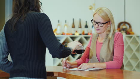 A-Woman-Tastes-Wine-In-A-Small-Winery-Communicates-With-The-Seller