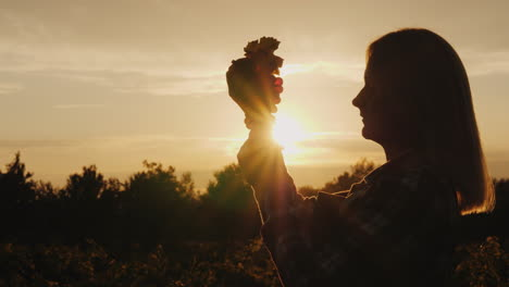 Silhouette-Of-A-Farmer-Holding-A-Bunch-Of-Grapes-In-His-Hands-Against-The-Setting-Sun