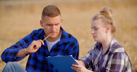 Agriculture-Female-And-Male-Farmers-Talking-At-Wheat-Field-During-Harvesting-3