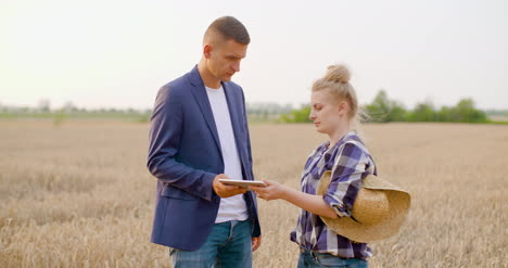 Agriculture-Female-And-Male-Farmers-Talking-At-Wheat-Field-During-Harvesting-7