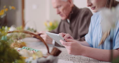 Young-Woman-Surfing-Internet-With-Grandfather-On-Digital-Tablet-7