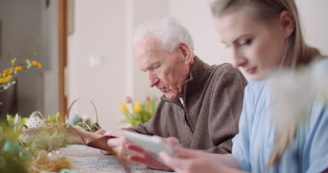 Young-Woman-Surfing-Internet-With-Grandfather-On-Digital-Tablet-8