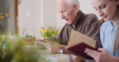 Young-Woman-Surfing-Internet-With-Grandfather-On-Digital-Tablet-10