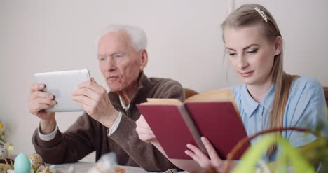 Young-Woman-Surfing-Internet-With-Grandfather-On-Digital-Tablet-2
