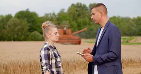 Agriculture-Female-And-Male-Farmers-Talking-At-Wheat-Field-During-Harvesting-10