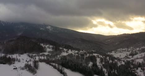 Aerial-View-Of-Mountains-And-Forest-Covered-With-Snow-At-Sunset-In-Winter
