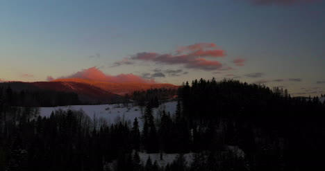 Aerial-View-Of-Mountains-And-Forest-Covered-With-Snow-At-Sunset-In-Winter-1