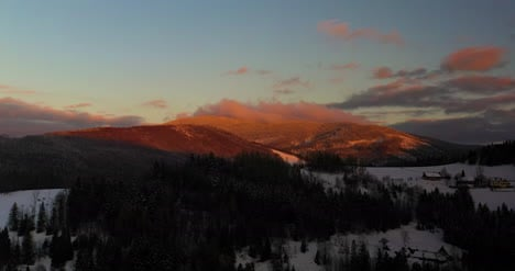 Aerial-View-Of-Mountains-And-Forest-Covered-With-Snow-At-Sunset-In-Winter-3