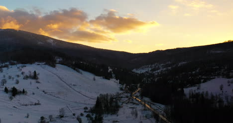 Aerial-View-Of-Mountains-And-Forest-Covered-With-Snow-At-Sunset-In-Winter-4