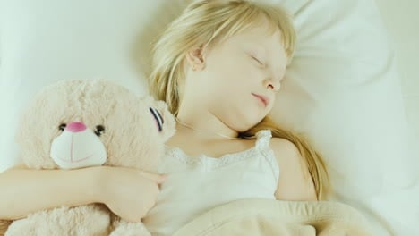 Little-Girl-Sleeping-In-Bed-Cuddles-A-Toy-Bear-Top-View