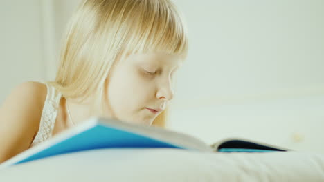 Little-Blonde-Girl-Reading-A-Book-In-Bed-4K-Video-26