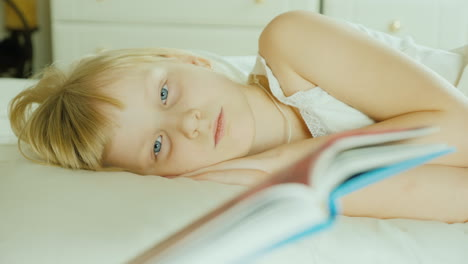 Little-Blonde-Girl-Reading-A-Book-In-Bed-4K-Video-28