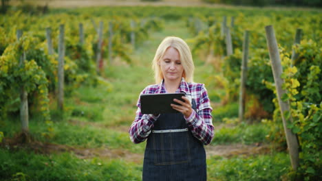 A-Satisfied-Female-Farmer-Uses-A-Tablet-Near-His-Garden-Evening-Before-Sunset
