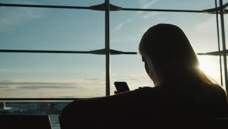 The-Silhouette-Of-A-Woman-Sitting-Facing-A-Large-Window-In-The-Airport-Terminal-Uses-A-Smartphone-Wa