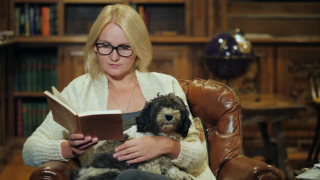 A-Woman-Relaxes-In-A-Luxurious-Home-Library-Holds-A-Small-Dog