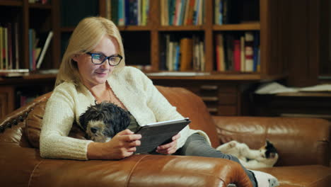 The-Woman-Uses-The-Tablet-At-Home-She-Has-A-Puppy-In-Her-Arms-And-In-The-Background-A-Cat-Plays-With