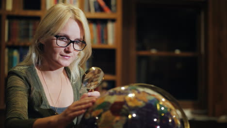 A-Woman-Looks-At-A-Beautiful-Globe-In-The-Library