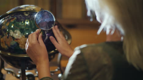 Woman-With-Magnifying-Glass-In-Hand-Examines-Big-Globe-Back-View