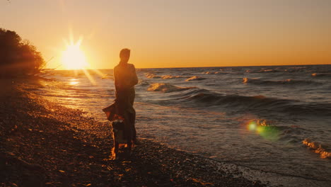 A-Young-Woman-Walks-With-A-Dog-On-The-Shore-Of-Lake-Ontario-At-Sunset-Windy-Weather-Beautiful-Sunset