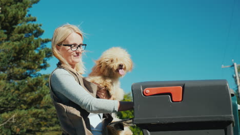 A-Young-Woman-With-A-Small-Dog-In-Her-Arms-Picks-Up-Letters-From-A-Mailbox