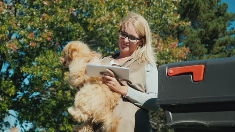 A-Woman-With-A-Dog-In-Her-Arms-Looks-Through-Correspondence-Near-The-Mailbox