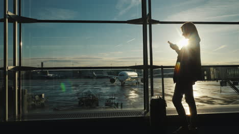 Passenger-With-A-Smartphone-In-The-Airport-Terminal-The-Silhouette-Illuminates-The-Sun-Behind-The-La