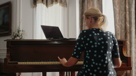 Woman-Learning-To-Play-The-Piano-Looking-At-Laptop-Screen