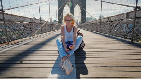 A-Young-Woman-Sits-On-The-Brooklyn-Bridge-In-New-York-Uses-A-Smartphone