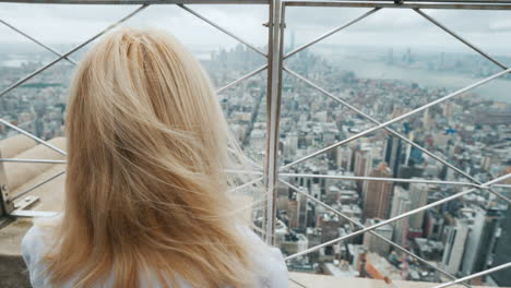 A-Woman-Looks-Through-The-Bars-On-The-Panorama-Of-New-York-One-In-A-Big-City-Concept