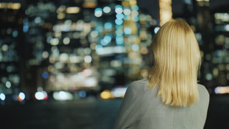 Blonde-Woman-Looking-At-The-Night-City-Rear-View