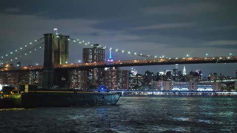 Cargo-Barge-Sails-Under-The-Brooklyn-Bridge-In-New-York-On-The-Background-Of-The-Night-Lights-Of-Man