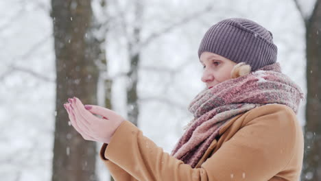A-Woman-Catches-Snowflakes-In-Her-Palms-Rejoices-In-The-Arrival-Of-Winter