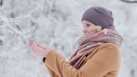 Attractive-Woman-Catches-Snowflakes-In-Her-Palms-Enjoys-Beautiful-Winter-Day