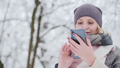 Young-Woman-Uses-Smartphone-In-Snow-Park