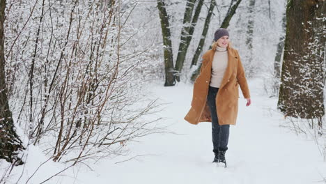 Stylish-Woman-Enjoys-A-Walk-In-The-Snowy-Forest