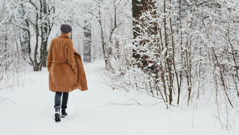 Active-Woman-In-Classic-Coat-Walks-Through-Snowy-Park