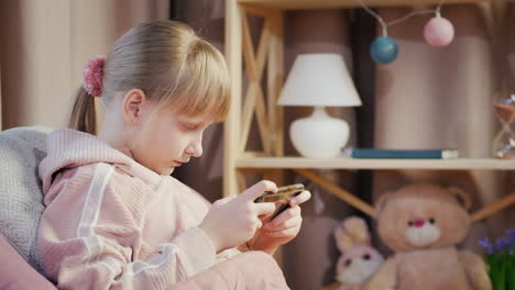 A-Child-Plays-On-A-Smartphone-In-His-Bedroom-Lies-In-Bed