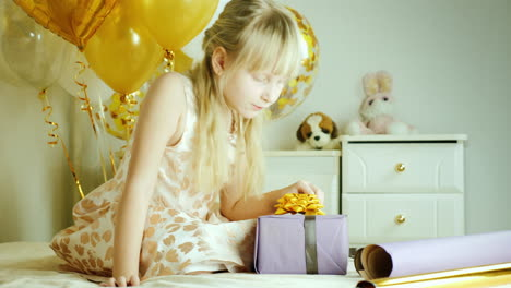 Blonde-Girl-7-Years-Wrapped-A-Box-Of-Gifts-In-Paper-Birthday-Gifts-Concept