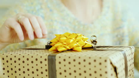 Female-Hands-Adjust-The-Ribbon-And-Bow-On-The-Box-With-A-Gift-Close-Up