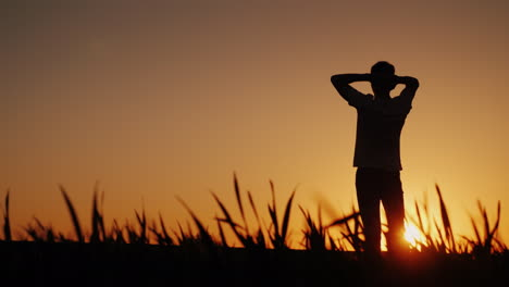 Silhouette-A-Young-Man-Enjoys-The-Fresh-Air-And-Admires-The-Sunset-He-Holds-His-Hands-Behind-The-Bac