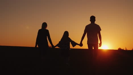 Parents-With-The-Child-Go-Forward-Towards-The-Sunset-Family-Silhouettes