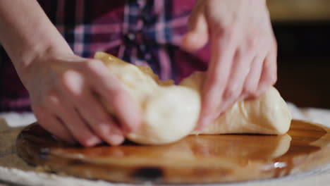 Close-Up---Hands-Knead-The-Dough-On-A-Wooden-Board-The-Board-Is-Oiled-With-Vegetable-Oil-4K-Video